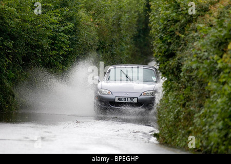 Cars make their way through flooded country lanes in the Murton district of Swansea today during the heavy downpours. - Stock Photo