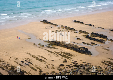 Couple on beach at Sandy Mouth near Bude Cornwall amongst eroded reefs of vertical rock strata covered in sand - Stock Photo