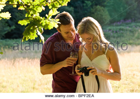 A young couple looking at photographs on their camera - Stock Photo