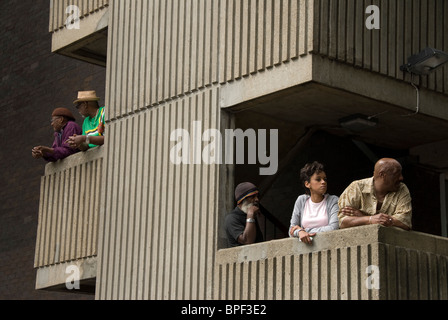 Residents in West London housing estate on their balconies watching Notting hill carnival going by. - Stock Photo