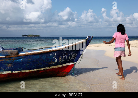 Kuna girl and wooden fishing boat on white sand beach , San Blas Islands , Panama - Stock Photo