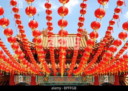 Many red Chinese lanterns hanging in rows above - Stock Photo