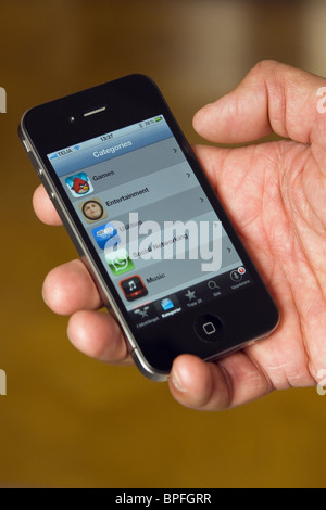 iPhone 4 in the palm of a hand, showing the app store. - Stock Photo