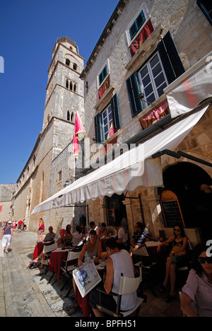 DUBROVNIK, CROATIA. A cafe on Stradun (Placa) in the old town, with the campanile of the Franciscan monastery behind. - Stock Photo