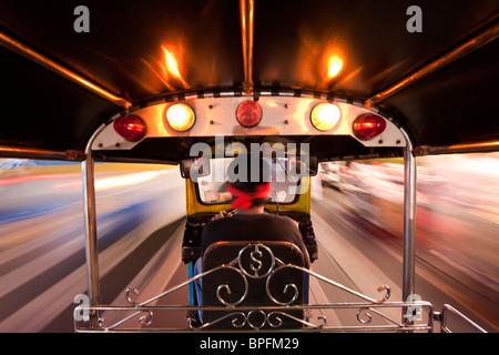 Tuk Tuk or auto rickshaw in motion at night, Bangkok, Thailand, Southeast Asia - Stock Photo