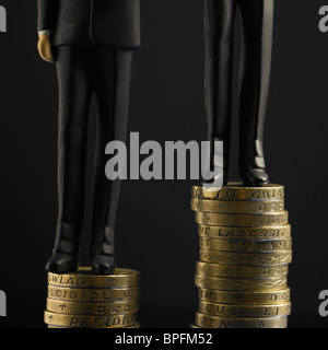 Two Figures In Black Suits Standing On Top Of Two Piles Of Pound Sterling Coins - Stock Photo