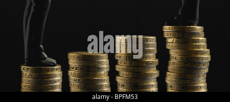 Two Figures In Black Suits Standing On Top Of Unequal Piles Of Pound Sterling Coins - Stock Photo