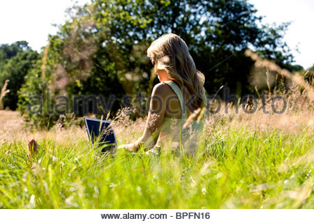 A young woman sitting on the grass, using a laptop - Stock Photo