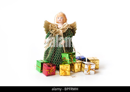 Pretty Christmas angel in a green dress with small coloured foil wrapped presents on a white background - Stock Photo