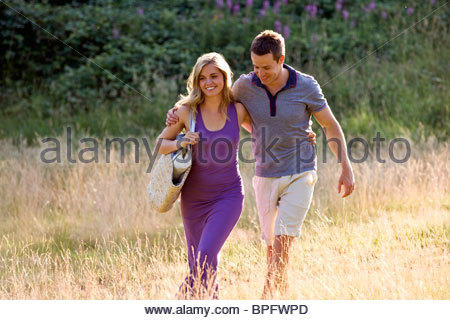 A young couple walking through a field arm in arm - Stock Photo