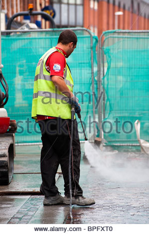 Rear view workman using a power jet washer to clean a building site in Hereford, UK. Man using high pressure jetwash - Stock Photo