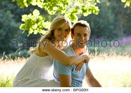 A young couple sitting on the grass, embracing - Stock Photo
