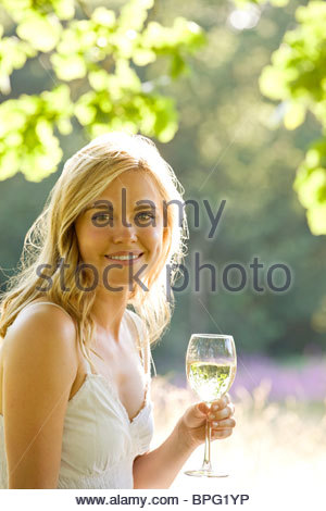 A young woman drinking a glass of white wine - Stock Photo