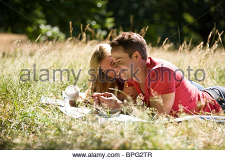 A young couple lying in the grass, relaxing - Stock Photo
