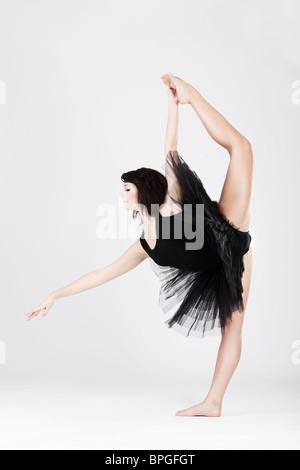 Beautiful female ballerina doing split against white background  - Stock Photo