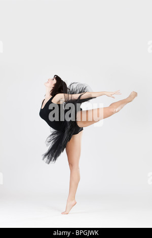 Beautiful female ballerina doing split against white background  - Stock Photo