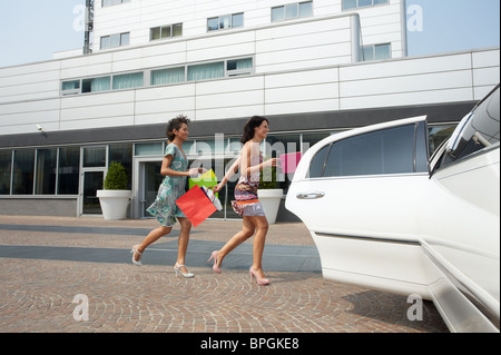 women running into car with shopping bags