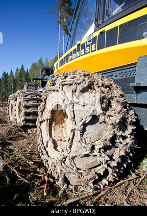 Dirty Ponsse Beaver forest harvester tyres with tire chains - Stock Photo