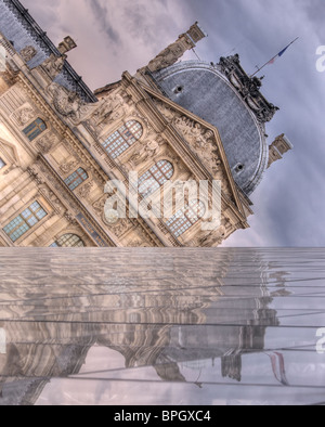 The Louvre reflects from I.M. Pei's Pyramid, as storm clouds gather above. One wall of the Pyramid forms a false - Stock Photo