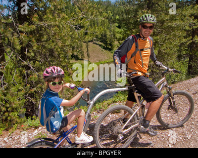 Man and child riding bikes. - Stock Photo