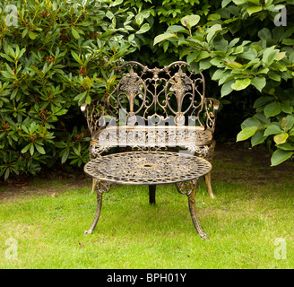 Old fashioned gold colored cast iron table and bench on formal lawn - Stock Photo