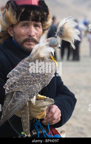 Kazakh hunter with Saker Falcon at Eagle hunters festival near Ulgii in western Mongolia October - Stock Photo