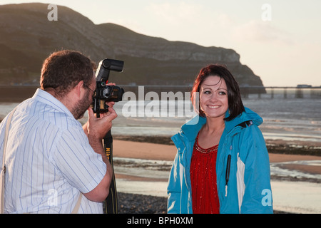 Photographer photographing a young female model smiling on the seafront using off camera flash. Wales, UK, Britain - Stock Photo
