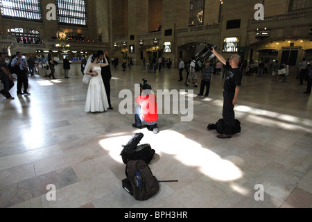 A bride and groom having their photo taken in Grand Central. New York. America - Stock Photo
