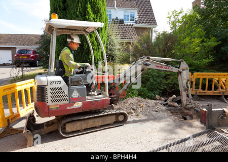 workers using a mini excavator to dig a trench in the road - Stock Photo