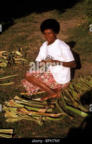 Rural Fijian woman preparing pandanus leaf to use as thatch - Stock Photo