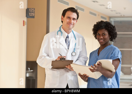 Doctor standing with a Jamaican female nurse - Stock Photo