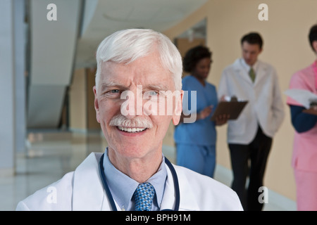 Doctor smiling with his colleagues in the background - Stock Photo
