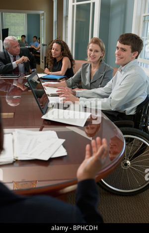 Businessman with spinal cord injury discussing with his colleague in a board room - Stock Photo