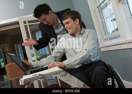 Businessman with spinal cord injury using a laptop with his colleague in an office - Stock Photo