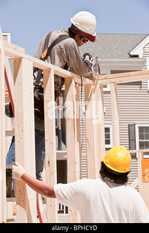 Carpenters sawing a wall stud - Stock Photo
