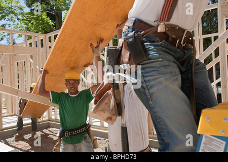 Carpenters lifting a laminated beam at a construction site - Stock Photo