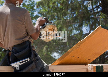 Carpenter sawing a beam at a construction site - Stock Photo