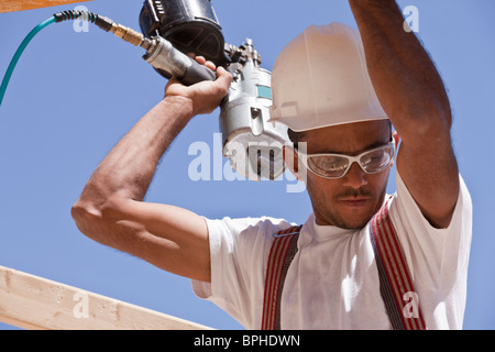 Carpenter using a nail gun - Stock Photo