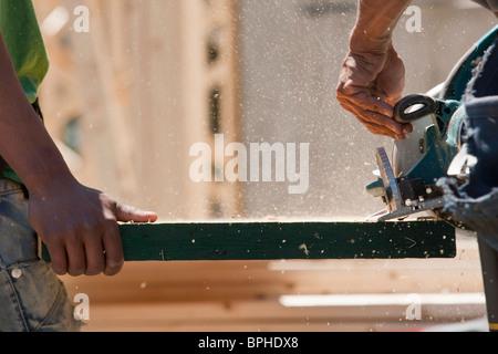 Carpenters sawing beam - Stock Photo