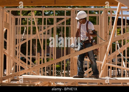 Carpenter standing at a construction site holding a nail gun - Stock Photo
