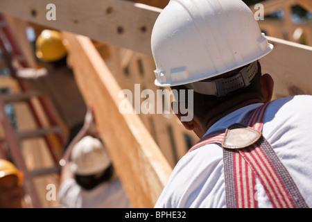 Carpenters lifting a beam - Stock Photo