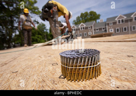 Bundle of nails with a carpenter using nail gun in the background - Stock Photo