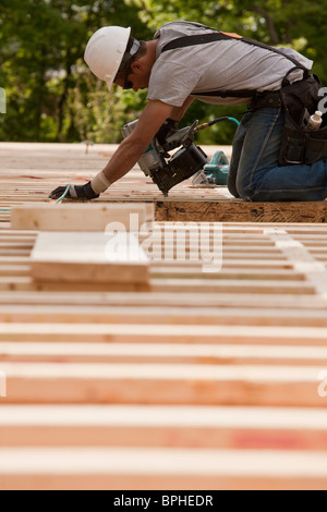 Carpenter using a nail gun at a construction site - Stock Photo