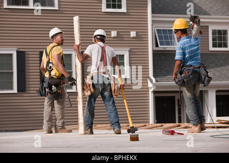 Carpenters working at a construction site - Stock Photo