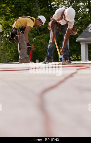 Carpenters working on particle board with power cord in foreground - Stock Photo