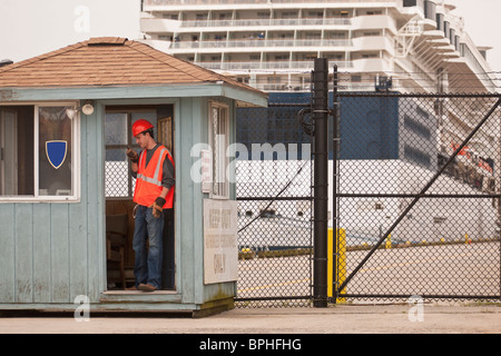 Engineer with a walkie-talkie at security point with a passenger ship in the background - Stock Photo