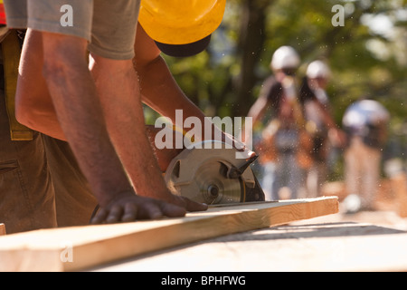 Carpenters using a circular saw at a construction site - Stock Photo