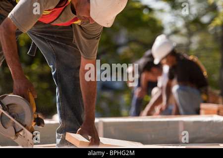 Carpenters using circular saw at a construction site - Stock Photo