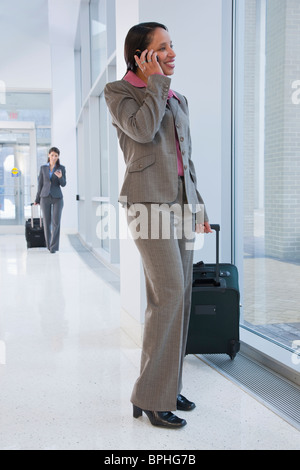 Hispanic businesswoman talking on a mobile phone at an airport
