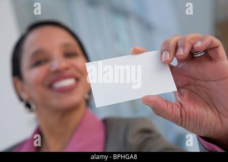 Hispanic businesswoman holding a blank card - Stock Photo